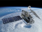 a large box-shaped satellite orbiting earth above a storm