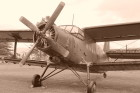 A black and white image of a vintage propeller aircraft on a runway