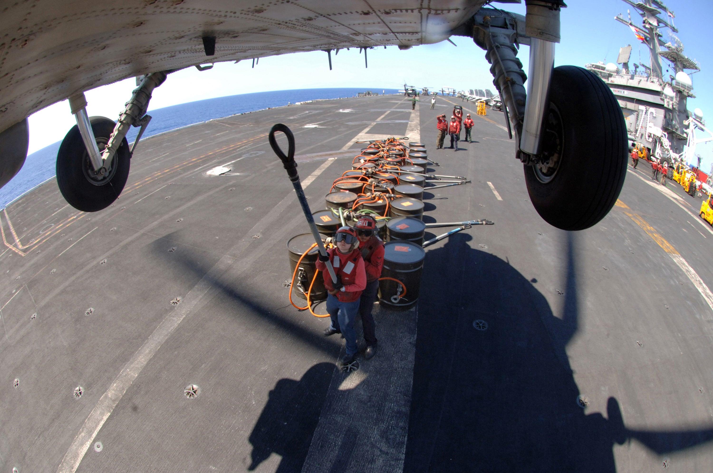 A U.S. Navy Sailor aboard USS Ronald Reagan (CVN 76) prepares to attach a cargo pendant to an SH-60 Seahawk heliocopter