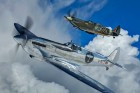A silver spitfire flying alongside a classic Royal Airforce version in the clouds