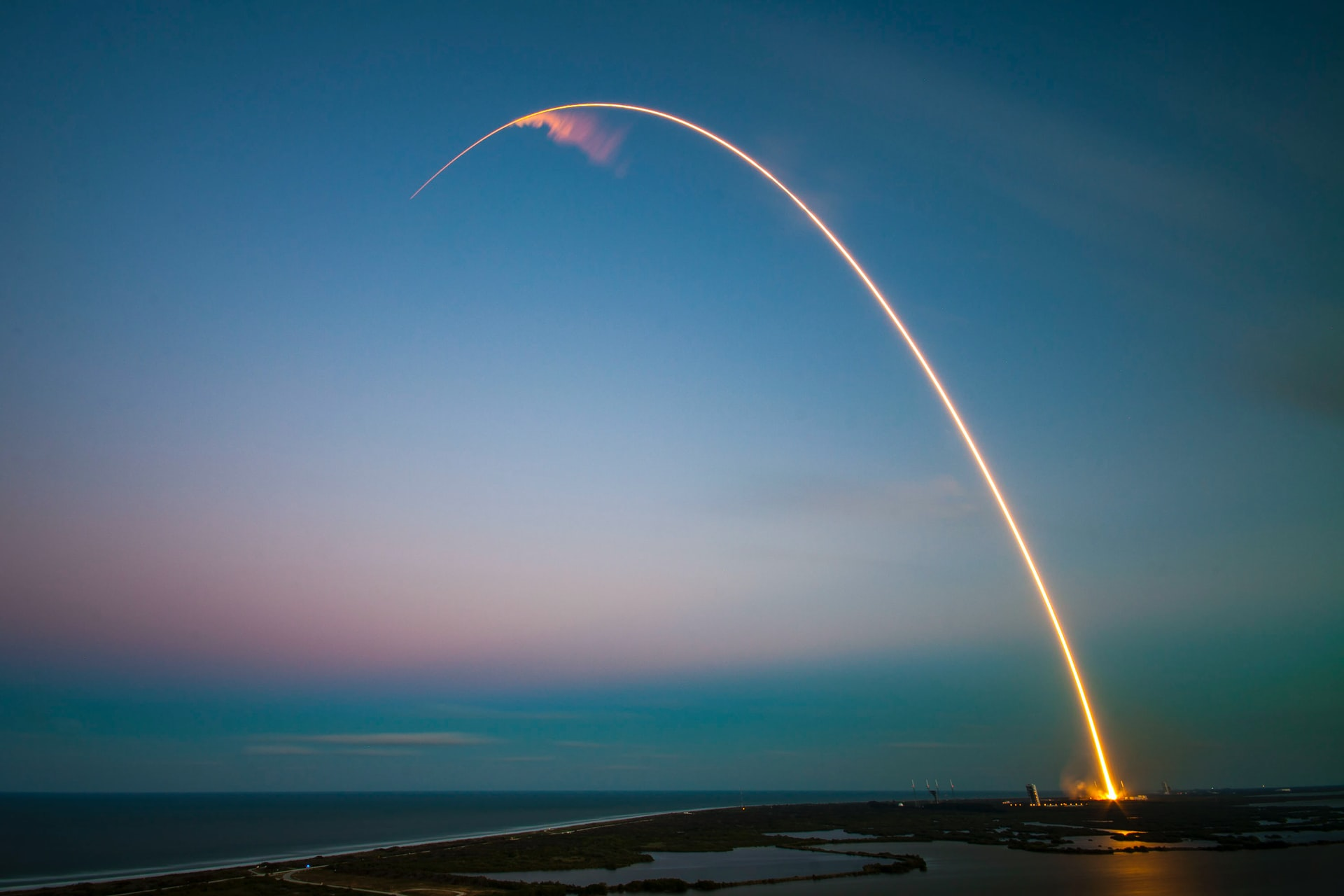 An arced trail from a rocket ship as it launches into space at dawn