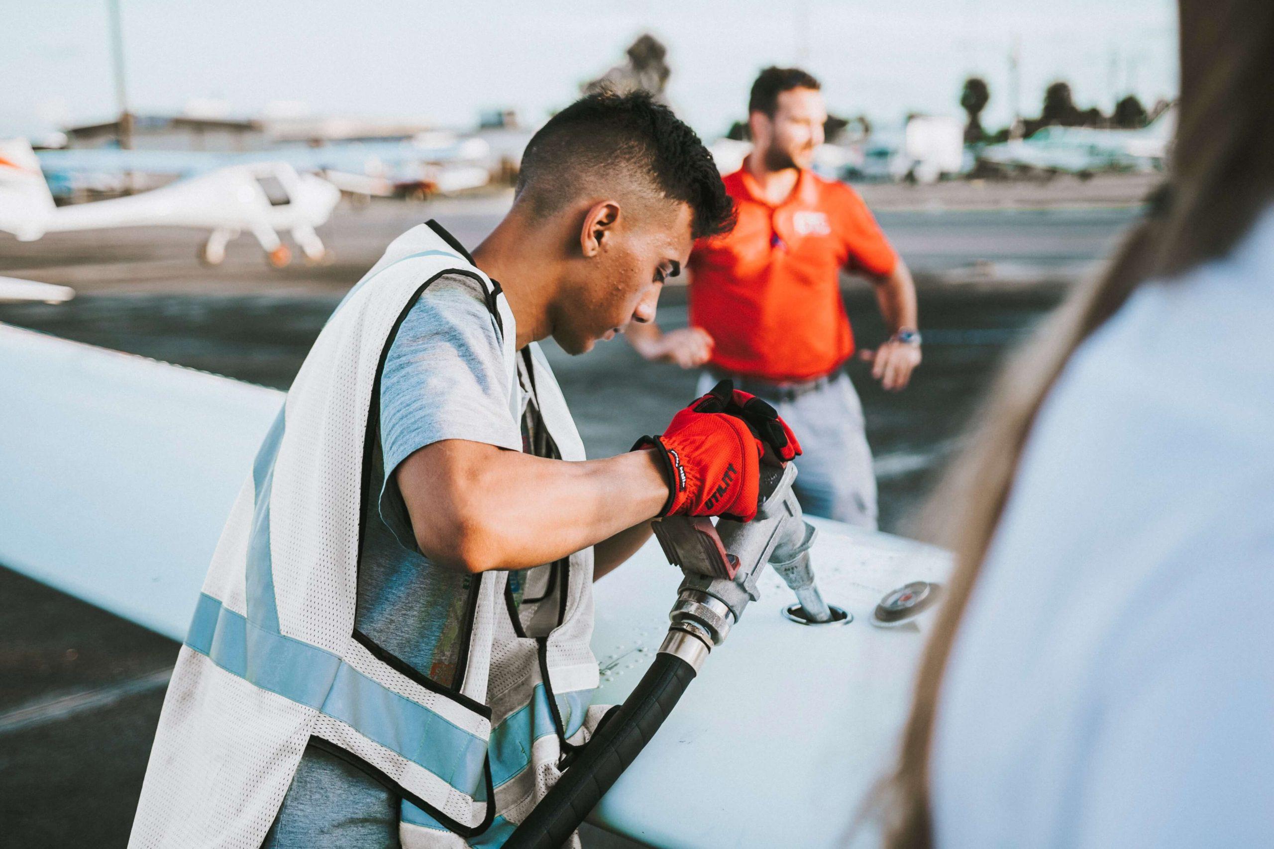A man refueling an aeroplane